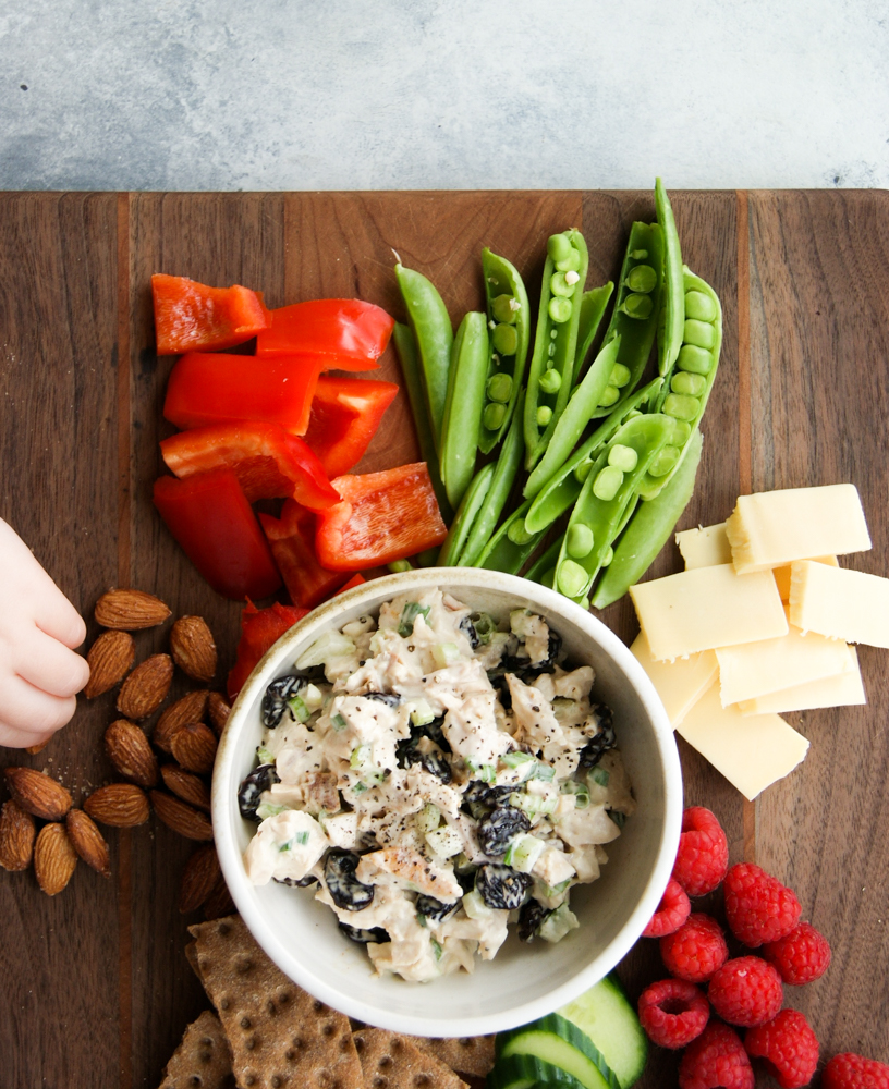 Chicken salad snack board with child's hand