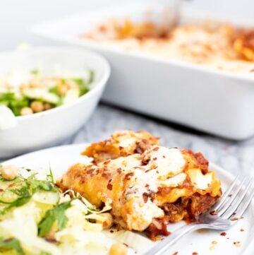 Slice of baked ravioli lasagna on a plate with salad