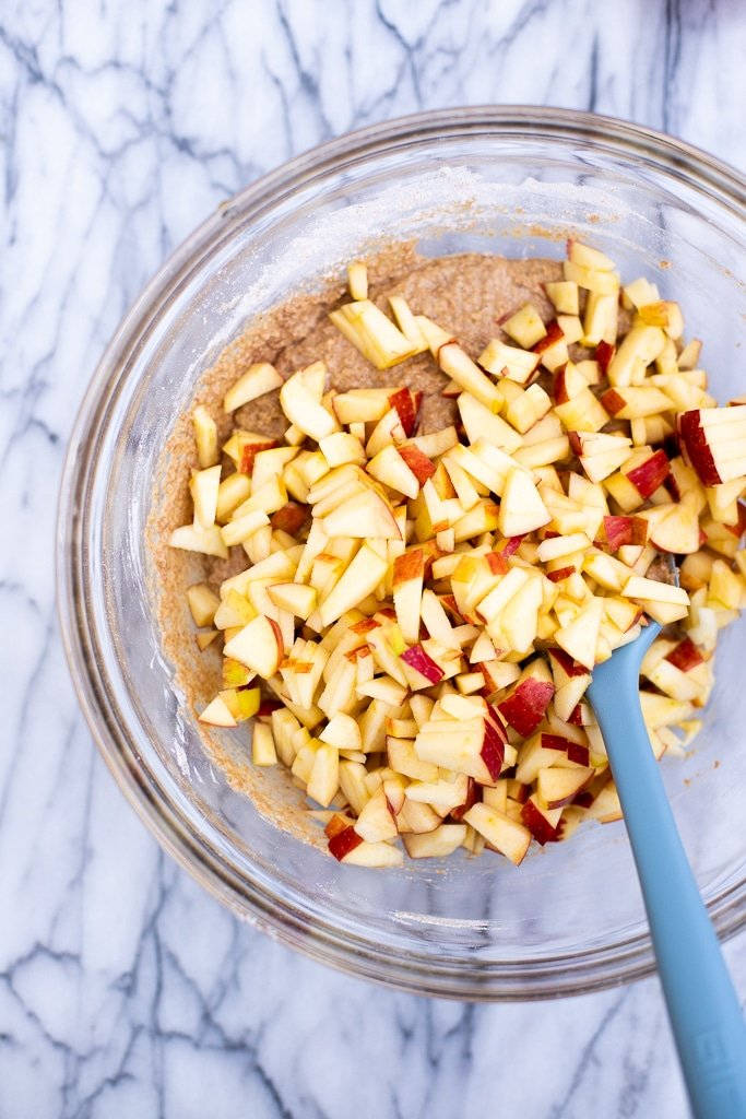 Mixing bowl with whole grain muffin batter and chopped apples