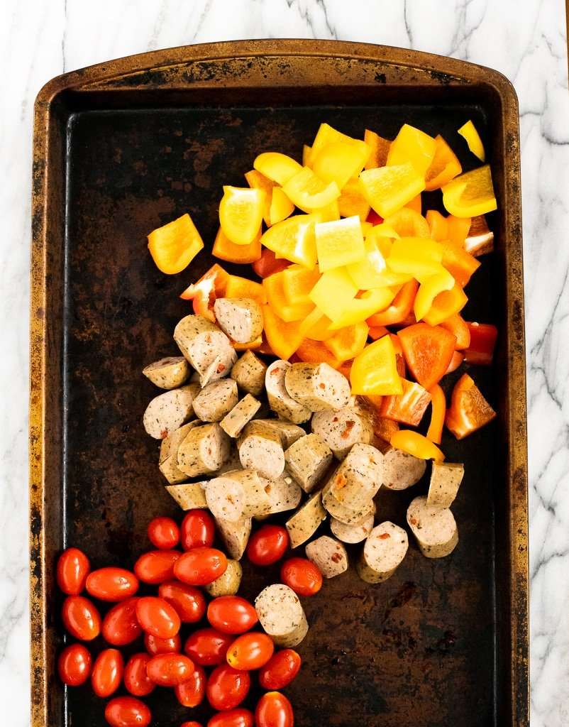 chicken sausage, peppers, and tomatoes on a sheet pan