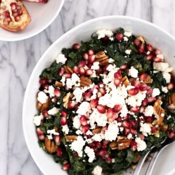 Kale pomegranate salad in a white bowl