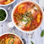 Three bowls of tortellini soup with sausage and fresh basil