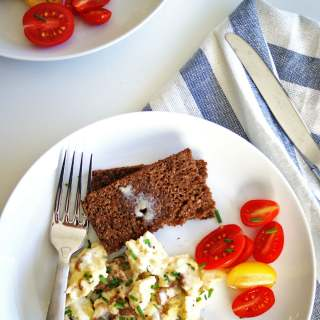 scrambled eggs with sour cream on a plate with toast and tomatoes