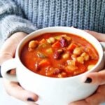person holding bowl of homemade minestrone soup