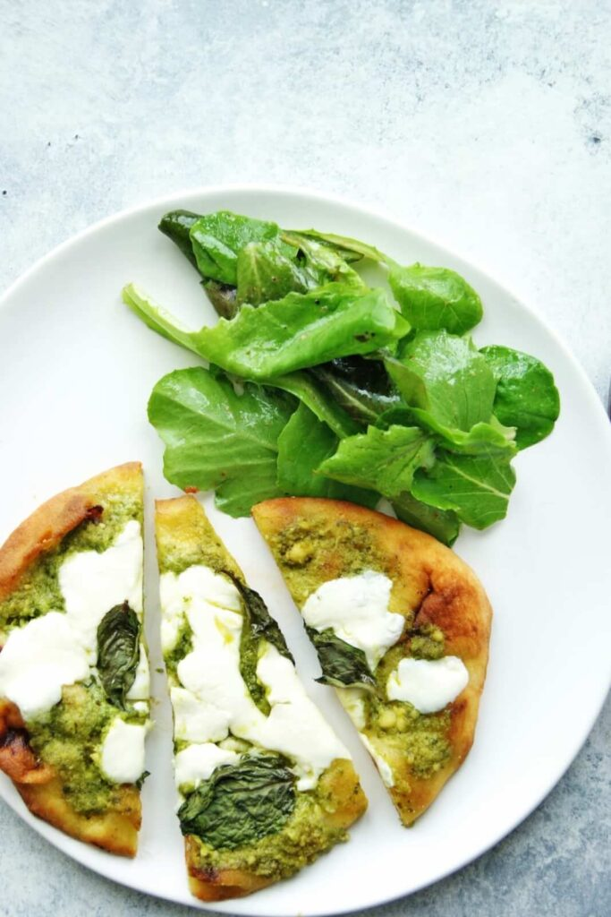 pesto naan pizza on a plate with salad