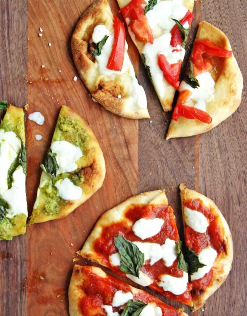 mini naan bread pizza with different toppings on cutting board