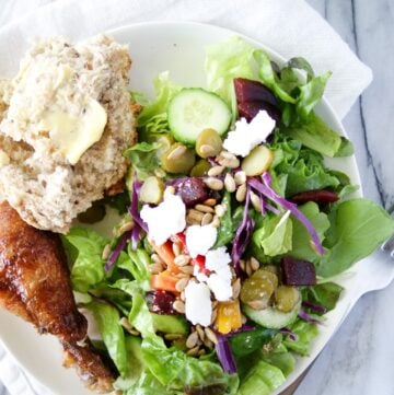 Side salad on a plate with chicken and bread