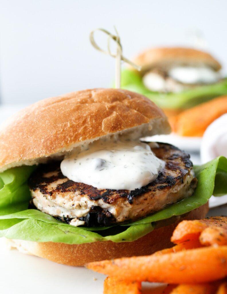 Salmon burger with dill sauce on bun