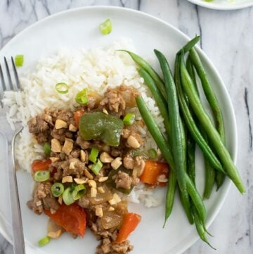 Plate with ground turkey stir fry over rice with green beans