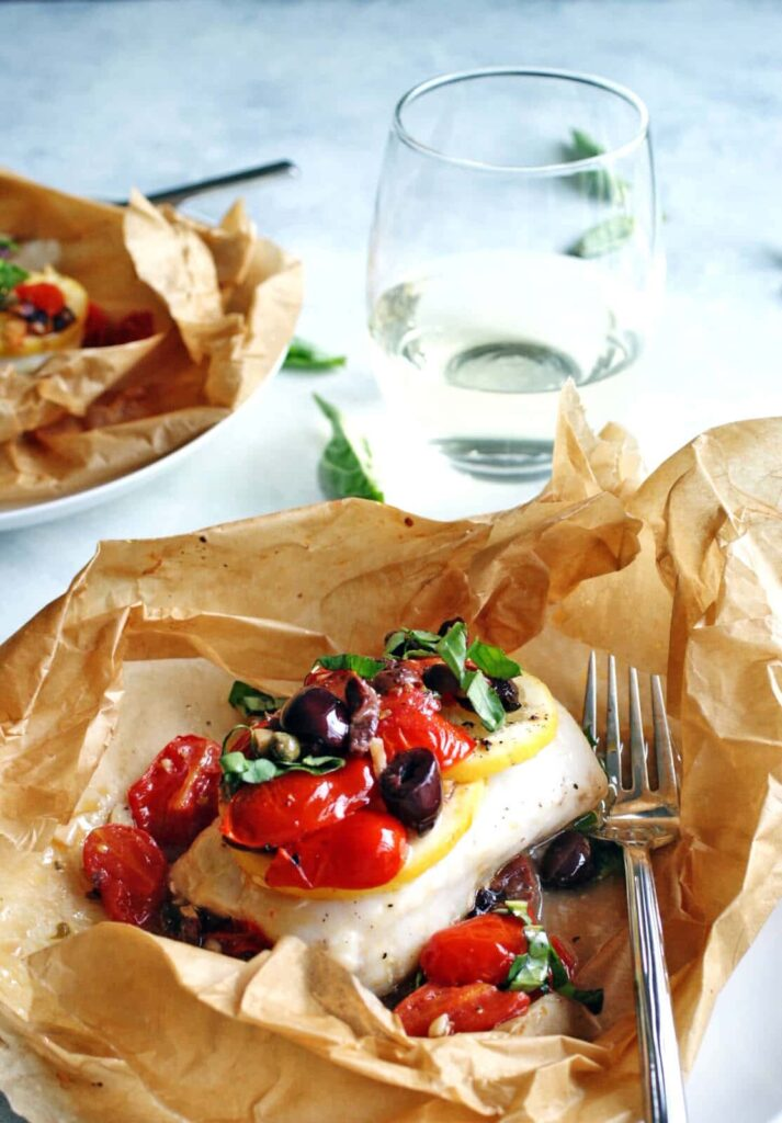 Mediterranean Baked Fish in parchment paper with a fork