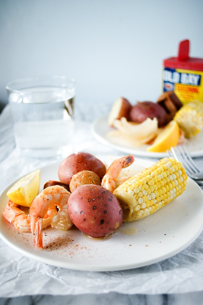 Plate with low country shrimp boil recipe and water