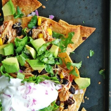 Tray of crock pot chicken nachos with fresh toppings