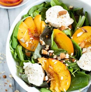 Peach burrata salad in a white bowl