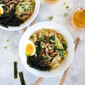 Two bowls of vegetarian ramen with chopsticks