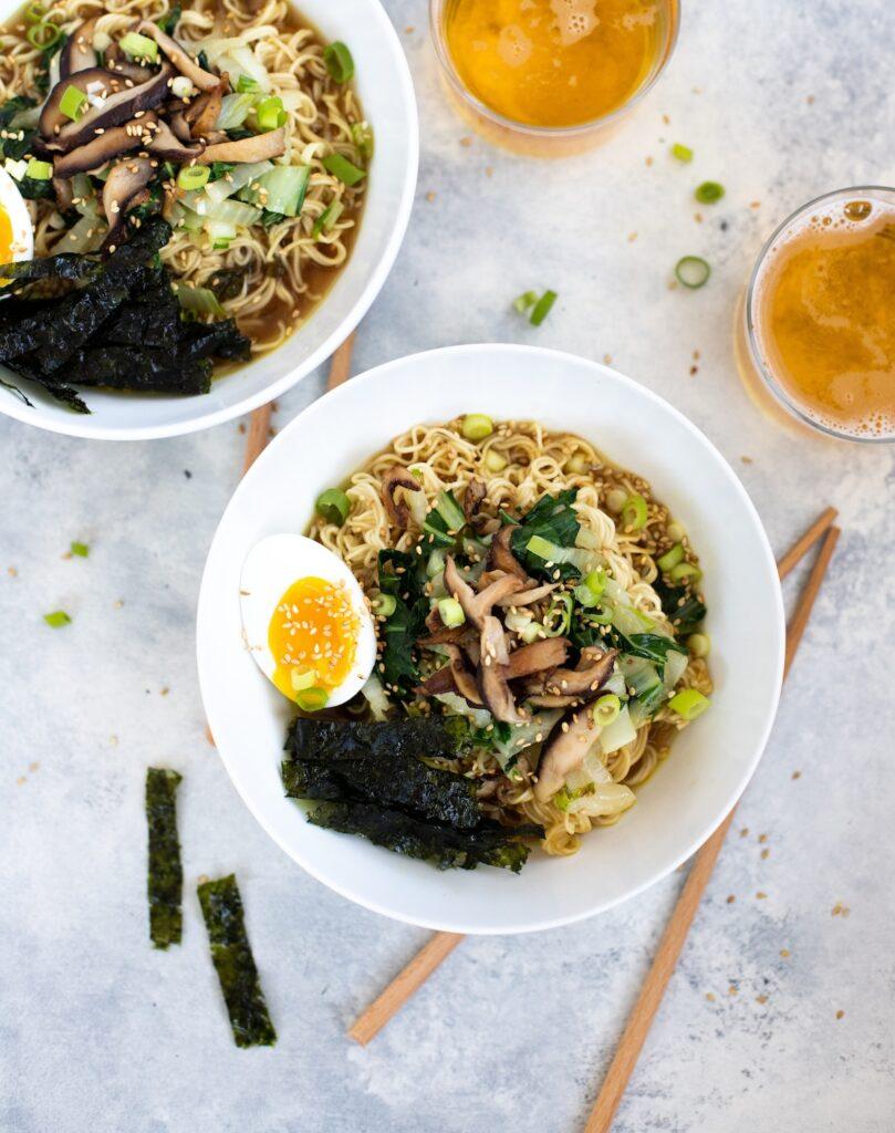 Two bowls of vegetarian ramen with chopsticks