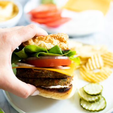 Hand holding veggie burger with chips on the side